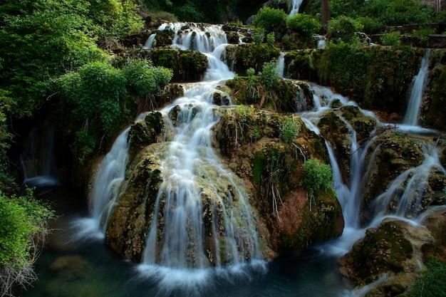 Prachtige waterval stroomt door een weelderig groen bos Gratis Foto