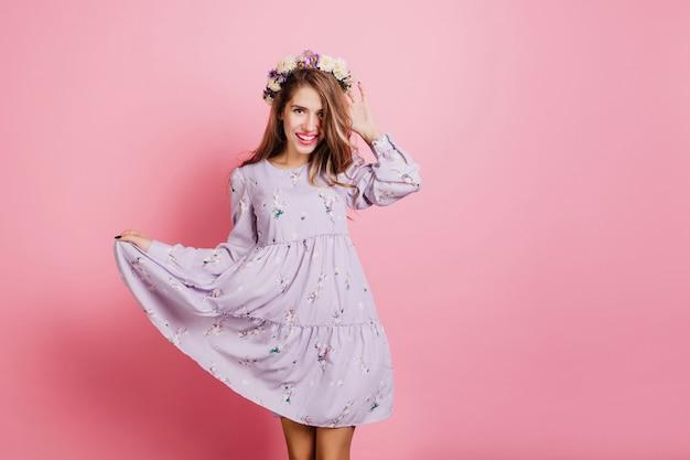 Prachtige witte vrouw in vintage paarse jurk poseren in studio Gratis Foto