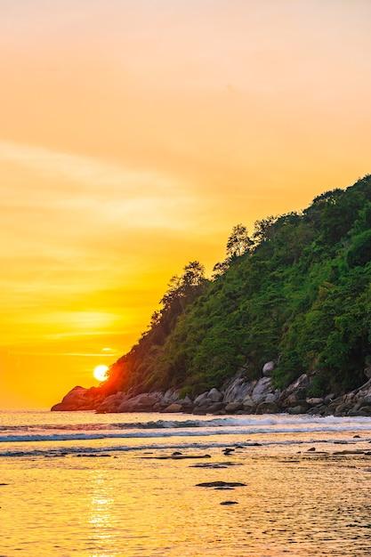 Prachtige zonsondergang over berg rond strand zee oceaan en rock Gratis Foto