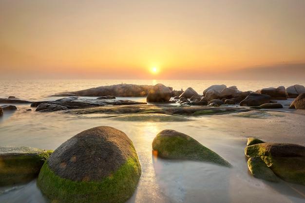 Prachtige zonsondergang over zee met rotsen bedekt met groen mos Premium Foto