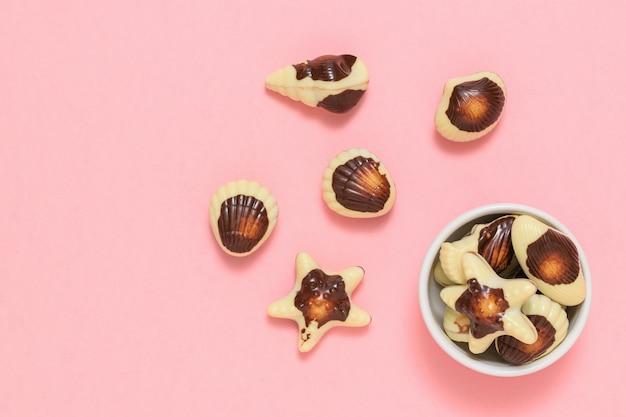 Pralines in de vorm van schelpdieren en schelpen. de zoetheid van melkchocolade. het uitzicht vanaf de top. plat leggen. Premium Foto