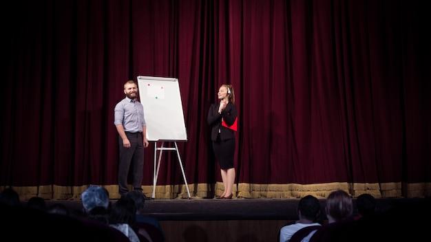 Praten met studenten. vrouwelijke spreker die presentatie geeft in hal op workshop. zakencentrum. achteraanzicht van deelnemers aan publiek. conferentie-evenement, training. Gratis Foto