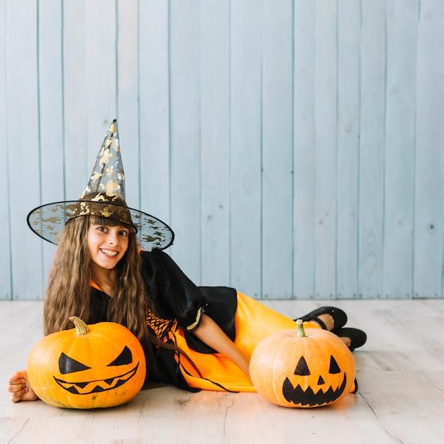 Pre-tienermeisje in heksenkostuum die op vloer met pompoenen liggen Gratis Foto