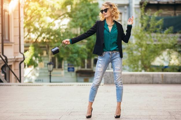 Preety stijlvolle vrouw lopen in de straat in spijkerbroek jas en groene blouse, mode accessoires, elegante stijl, modetrends van de lente dragen Gratis Foto