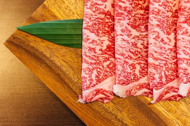 Premium rare slices wagyu a5-rundsvlees met een hoge marmerstructuur op vierkante houten plaat Premium Foto