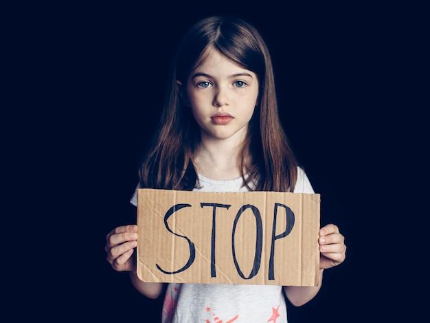 Preteen meisje houdt een teken stop, concept van problemen, negatieve emoties, verslaving van kinderen en adolescenten Premium Foto