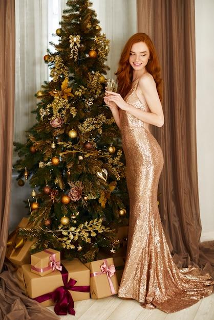 Prettige kerstdagen en een gelukkig nieuwjaarsvakantie! de vrolijke leuke jonge vrouw bevindt zich dichtbij vakantieboom met stelt voor. Premium Foto