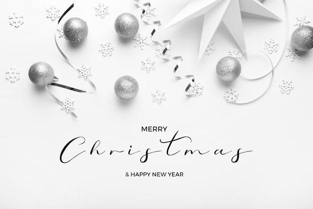 Prettige kerstdagen en gelukkig nieuwjaar greetins met zilveren tinten op een elegante witte achtergrond Gratis Foto