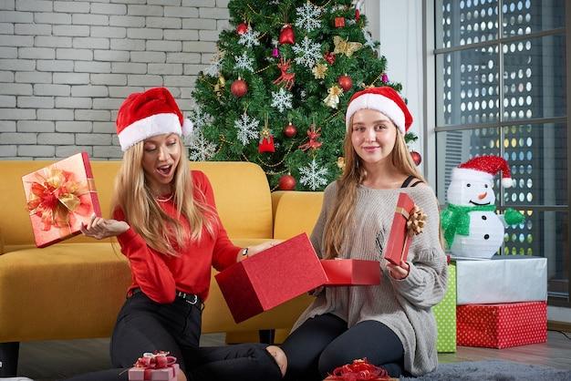 Prettige kerstdagen en gelukkig nieuwjaar vakantie, mooie witte kaukasische vrouw vieren, geschenken uitwisselen ontspannen voor een gele bank en kerstboom op kamer Premium Foto