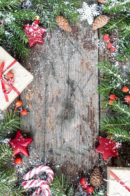 Prettige kerstdagen en gelukkige feestdagen wenskaart, frame, banner. nieuwjaar. nieuwjaarskaart met sneeuw op houten achtergrond. winter xmas vakantie thema. plat leggen. kopieer ruimte Gratis Foto