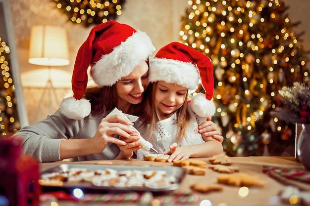 Prettige kerstdagen en prettige feestdagen. moeder en dochter kokende kerstmiskoekjes. Premium Foto