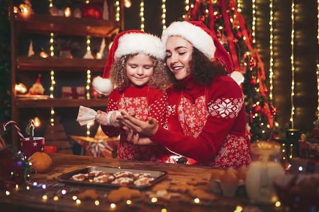 Prettige kerstdagen en prettige feestdagen. vrolijk schattig krullend meisje en haar oudere zus in santa hoeden koken kerstkoekjes. Premium Foto