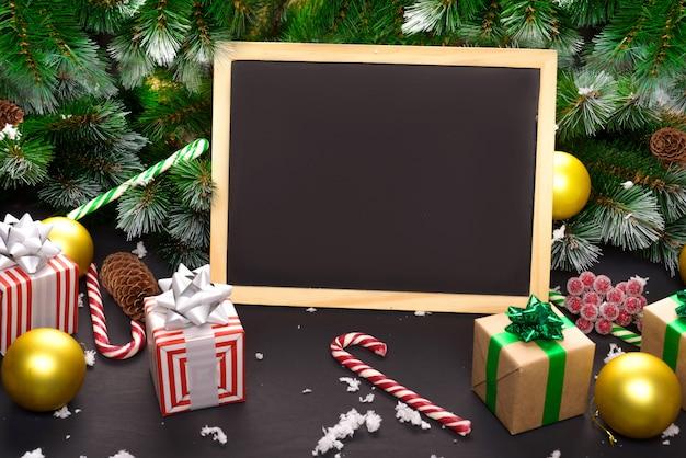 Prettige kerstdagen of gelukkig nieuwjaar frame samenstelling. spartakken, kerstmisspeelgoed, geschenkdoos, pluizige sneeuw, dennenappels, snoep en winterbessen op zwarte achtergrond. plat lag, kopieer ruimte voor uw tekst. Premium Foto