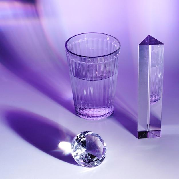 Prisma; fonkelende diamant en een glas water op paarse glanzende achtergrond Gratis Foto