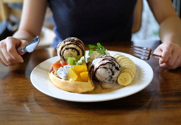 Probeert vork en mes te gebruiken om wafels te eten, geserveerd met gemengd fruit, in plakjes gesneden banaan Premium Foto