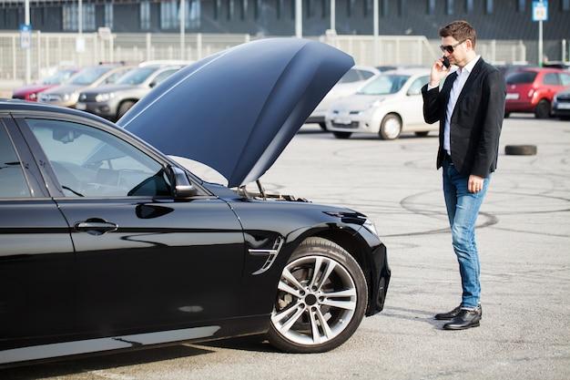 Problemen onderweg. mens die met gebroken auto smartphone uitnodigt Premium Foto