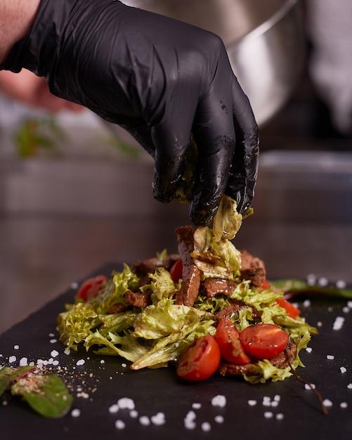 Proces om warme salade met kalfsvlees te koken. handen van een chef-kok in zwarte handschoenen. zwart leisteen bord. Premium Foto