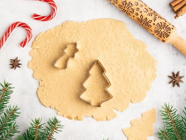 Proces van het bakken van traditioneel kerst- en nieuwjaarsdessert, peperkoekkoekjes, deegrol met sneeuwvlokkenpatroon, anijssterren en kaneel, kerstmis en winter, frame-indeling Premium Foto