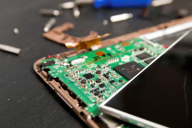 Proces van pc tablet apparaat reparatie in de buurt van schroevendraaier en bit. gedemonteerd worden. Premium Foto