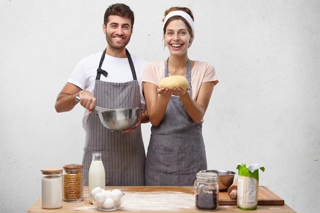 Producten, eten, keuken en kookconcept. portret van gelukkig positief jong europees paar die eigengemaakt brood bakken Gratis Foto