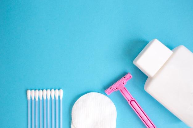 Producten voor persoonlijke verzorging van bovenaf bekijken. witte fles, scheermes, oorstokken, wattenschijfjes op blauwe rug Premium Foto