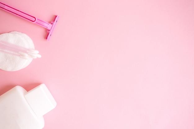 Producten voor persoonlijke verzorging. witte fles, scheermes, oorstokken, wattenschijfjes op roze achtergrond. c Premium Foto