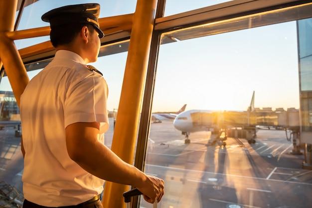 Proef in eenvormige status bij het instappen van poortgebied in luchthaventerminal die uit venster kijken om grondpersoneel te zien die een vliegtuig voorbereiden. Premium Foto