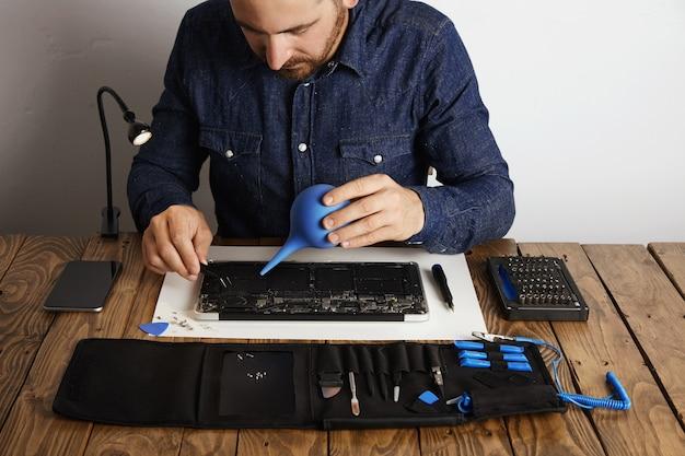 Professional werkt in zijn laboratorium om de computerlaptop toolkit-box met specifieke instrumenten in de buurt te repareren en schoon te maken Gratis Foto
