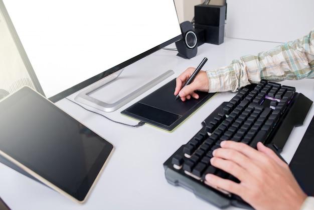 Professioneel fotograaf- en grafisch ontwerp werkt het bewerken van foto's in een tablet pen touch. editor retoucheert foto. wit scherm. Premium Foto