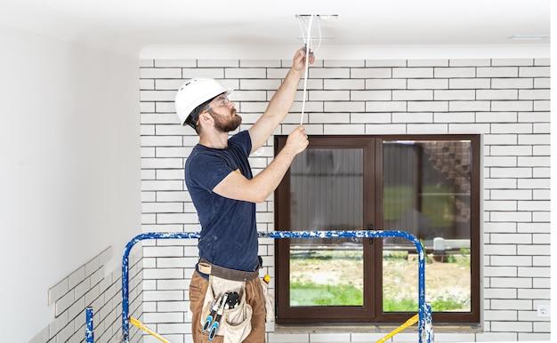 Professioneel in overall met gereedschap op de achtergrond van de reparatielocatie over de volle lengte. home renovatie concept. Gratis Foto