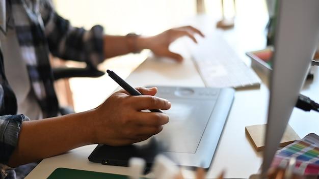 Professioneel mannetje die freelancer op tablet trekken tijdens nieuw project met bebouwd schot Premium Foto