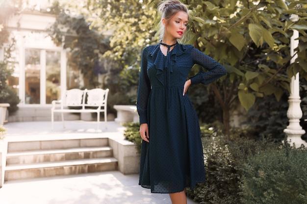 Professioneel model poseren in de achtertuin van het restaurant, groene jurk dragen, hand op de taille, tuin, buiten, make-up, haarbroodje, rode lippen Gratis Foto