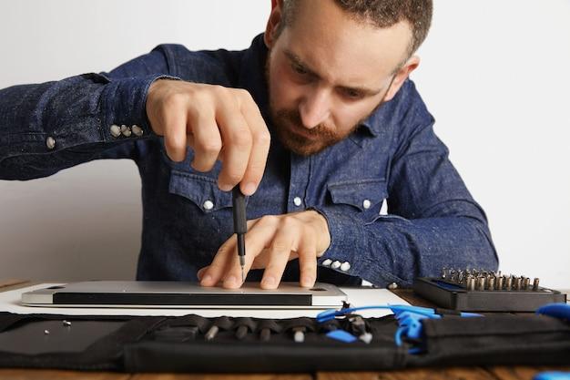 Professioneel nauwkeurig losschroeven van behuizing van metalen dunne laptop in zijn elektrische servicelaboratorium in de buurt van gereedschapstas om het schoon te maken en te repareren, vooraanzicht Gratis Foto
