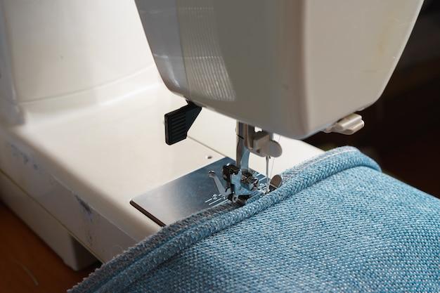 Professionele apparatuur. moderne naaimachine met speciale naaivoet. het proces van het naaien van een decoratief koord van blauw kledingstuk. Premium Foto