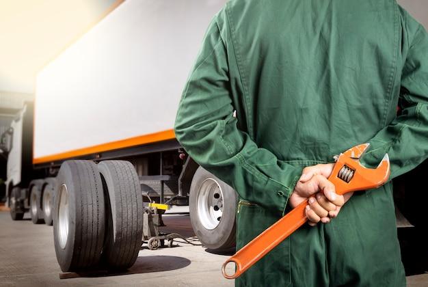 Professionele automonteur met grote sleutel voor onderhoud van de vrachtwagenwielen. Premium Foto