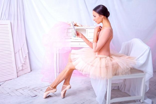 Professionele balletdanser die in de spiegel op roze kijkt Gratis Foto