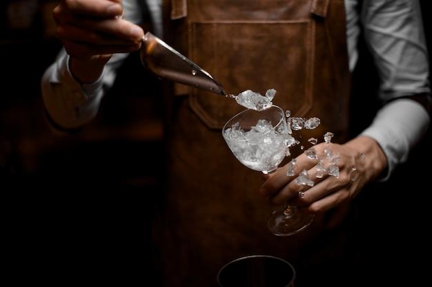 Professionele barman die gemalen ijs op het glas zetten Premium Foto