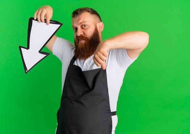 Professionele bebaarde kapper man in schort met grote pijl teken ermee en vinger naar beneden staande over groene muur Gratis Foto