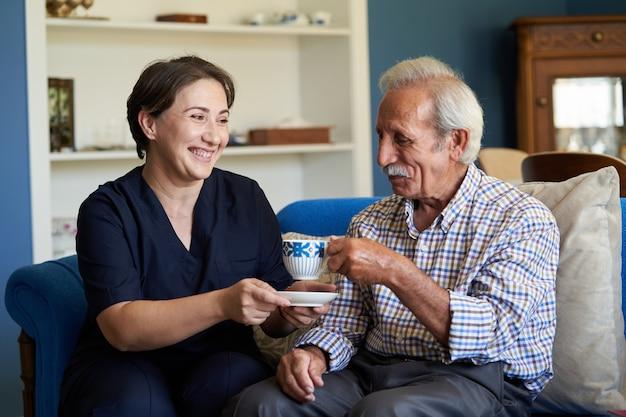 Professionele behulpzame verzorger en een senior man tijdens huisbezoek Premium Foto