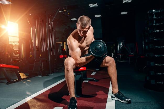 Professionele bodybuilder, oefeningen met halters in de sportschool, trainen op de biceps. motivatie. Premium Foto