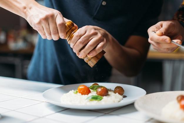 Professionele chef-kok bereidt verbazingwekkende smakelijke dampende gerecht van italiaanse risotto met parmezaanse kaas in designer hipster keuken Gratis Foto