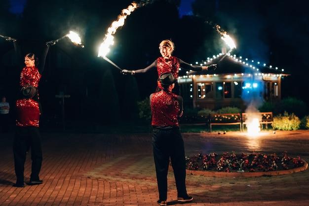 Professionele dansers mannen en vrouwen maken een vuurshow en pyrotechnische prestaties Premium Foto