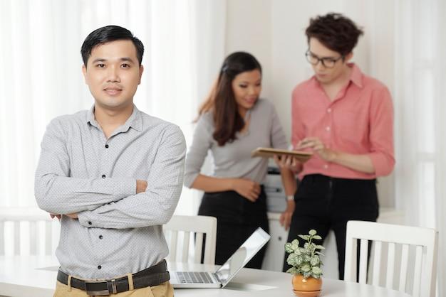 Professionele etnische werknemer met collega's in het kantoor Gratis Foto