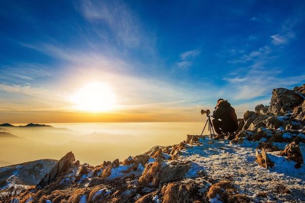 Professionele fotograaf maakt foto's met camera op statief op rotsachtige top bij zonsondergang Gratis Foto