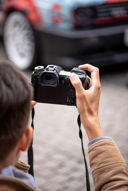 Professionele fotograaf maakt foto's van een auto op straat Premium Foto
