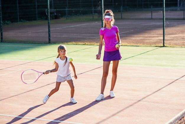 Professionele jonge coach gooit bal en kleine tennisser raakt bal voor racket tijdens training op het buitenveld. sport, gezondheidszorg concept. Premium Foto