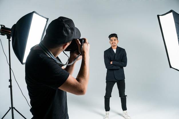 Professionele jonge fotograaf die foto's van indisch model in studio met licht nemen Gratis Foto