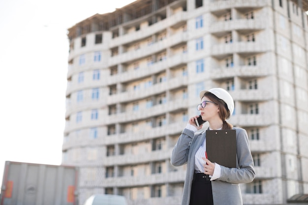 Professionele jonge vrouwelijke architect die op het klembord van de cellphoneholding bij bouwwerf spreekt Gratis Foto