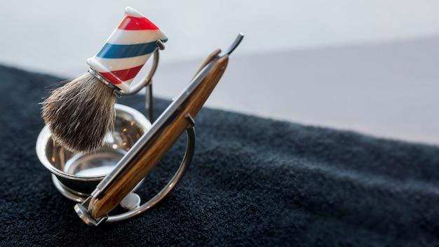 Professionele kapper die voor het scheren van baard op bureau wordt geplaatst Gratis Foto