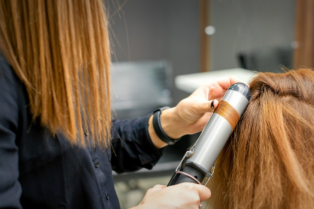 Professionele kapper maakt krullen met een krultang voor een jonge vrouw met lang rood haar in een schoonheidssalon Premium Foto